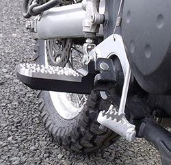 Lowered wide foot pegs with chamfered lower edge on Kawasaki KLR650 motorcycle